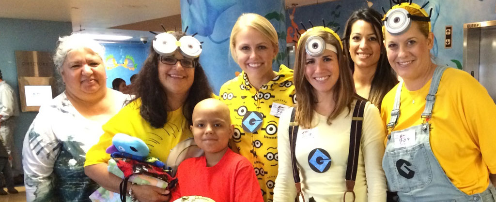 Employees wearing Minions costumes huddled around a young boy