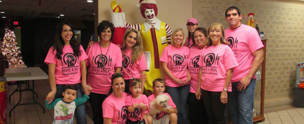 Group of people wearing pink shirts that say Share-A-Meal in front of Ronald McDonald statue in House