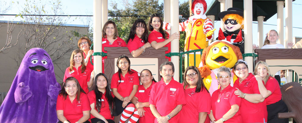 Employees wearing red shirts on playground with Ronald McDonald Characters