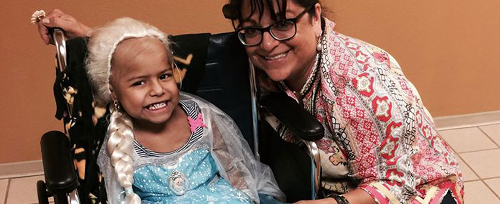 "Employee with young guest in wheelchair wearing ""Frozen"" Princess costume."