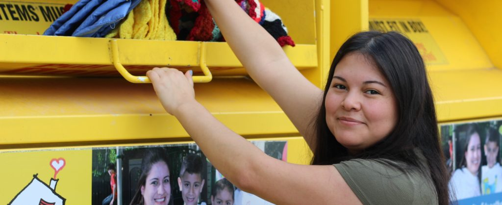 Young girl dropping clothing items in yellow metal donation bin for Ronald McDonald House