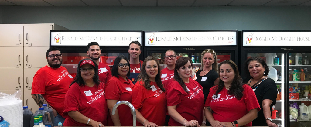 Bank employees in red shirts posing for a picture in the kitchen