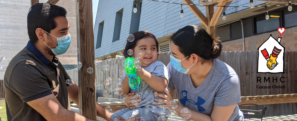 Dad, baby and mom blowing bubbles outside